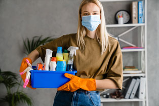woman in face mask with cleaning supplies